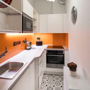 Diseño de cocina en L, minimalista, pequeña, cerrada, sin isla, con fregadero de un seno, armarios con paneles lisos, puertas de armario blancas, encimera de laminado, salpicadero naranja, salpicadero de vidrio templado, electrodomésticos de acero inoxidable, suelo de baldosas de porcelana y suelo multicolor