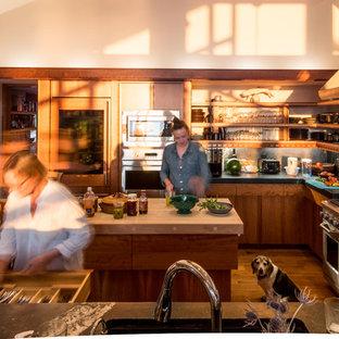 Rustic u-shaped kitchen/diner in Richmond with open cabinets, medium wood cabinets, soapstone worktops, grey splashback, stone slab splashback, stainless steel appliances, light hardwood flooring and an island.