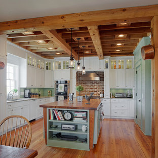 Photo of a large beach style u-shaped eat-in kitchen in Charleston with an undermount sink, louvered cabinets, white cabinets, granite benchtops, stainless steel appliances, medium hardwood floors and with island.