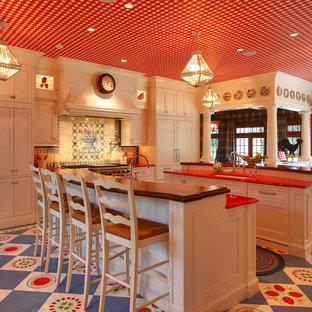 Стильный дизайн: кухня в классическом стиле с врезной раковиной, фасадами с утопленной филенкой, бежевыми фасадами, деревянной столешницей, разноцветным фартуком, техникой под мебельный фасад, разноцветным полом и красной столешницей - последний тренд