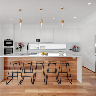 This is an example of a large modern l-shaped kitchen in Sydney with an undermount sink, flat-panel cabinets, white cabinets, quartz benchtops, white splashback, glass sheet splashback, stainless steel appliances, with island, brown floor, white benchtop and medium hardwood floors.