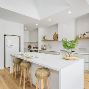This is an example of a beach style single-wall eat-in kitchen in Melbourne with an undermount sink, white splashback, stainless steel appliances, with island, white benchtop and vaulted.