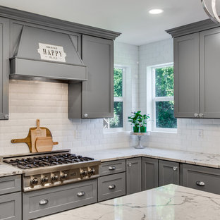 Inspiration for a large traditional l-shaped kitchen/diner in Portland with a belfast sink, shaker cabinets, grey cabinets, engineered stone countertops, white splashback, ceramic splashback, stainless steel appliances, plywood flooring, an island, brown floors and white worktops.