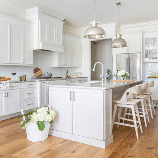 Coastal kitchen remodeling - Inspiration for a coastal l-shaped light wood floor and beige floor kitchen remodel in Jacksonville with a farmhouse sink, shaker cabinets, white cabinets, white backsplash, subway tile backsplash, stainless steel appliances, an island and beige countertops