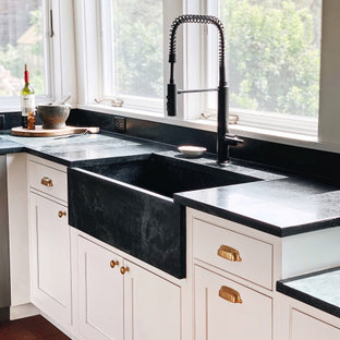 Mid-sized country l-shaped kitchen in New York with a farmhouse sink, beaded inset cabinets, white cabinets, soapstone benchtops, stainless steel appliances, ceramic floors, with island, red floor and black benchtop.