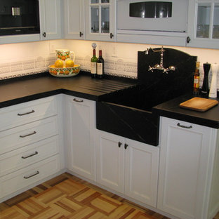 Photo of a mid-sized traditional u-shaped separate kitchen in Tampa with an integrated sink, recessed-panel cabinets, white cabinets, soapstone benchtops, multi-coloured splashback, ceramic splashback, light hardwood floors, no island and multi-coloured floor.