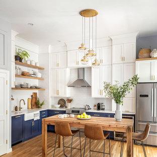 ボストンのトランジショナルスタイルのおしゃれなキッチン (青いキャビネット、白いキッチンパネル、セラミックタイルのキッチンパネル、無垢フローリング、エプロンフロントシンク、シェーカースタイル扉のキャビネット、アイランドなし、茶色い床、白いキッチンカウンター) の写真
