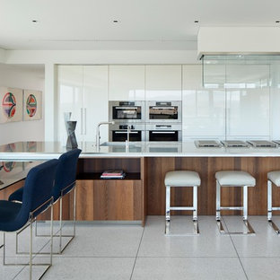 This is an example of a contemporary kitchen in Orange County with flat-panel cabinets, white cabinets, stainless steel appliances and multiple islands.