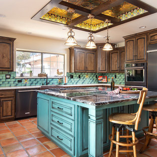 Large southwestern eat-in kitchen inspiration - Large southwest u-shaped terra-cotta floor and orange floor eat-in kitchen photo in Los Angeles with a farmhouse sink, raised-panel cabinets, quartz countertops, green backsplash, ceramic backsplash, an island, dark wood cabinets, white countertops and black appliances