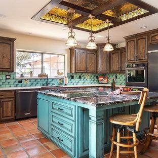 Свежая идея для дизайна: большая п-образная кухня в стиле фьюжн с обеденным столом, раковиной в стиле кантри, фасадами с выступающей филенкой, столешницей из кварцевого агломерата, зеленым фартуком, фартуком из керамической плитки, полом из терракотовой плитки, островом, оранжевым полом, темными деревянными фасадами, белой столешницей и черной техникой - отличное фото интерьера