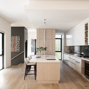 This is an example of a contemporary galley kitchen in Perth with an undermount sink, flat-panel cabinets, white cabinets, black splashback, panelled appliances, medium hardwood floors, with island, brown floor and white benchtop.