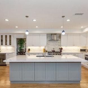 ロサンゼルスの中サイズのコンテンポラリースタイルのおしゃれなキッチン (アンダーカウンターシンク、シェーカースタイル扉のキャビネット、白いキャビネット、クオーツストーンカウンター、ベージュキッチンパネル、石タイルのキッチンパネル、シルバーの調理設備の、淡色無垢フローリング、黄色い床、白いキッチンカウンター) の写真