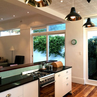 Design ideas for a traditional galley eat-in kitchen in Other with an undermount sink, flat-panel cabinets, white cabinets, granite benchtops, green splashback, glass tile splashback, stainless steel appliances and medium hardwood floors.
