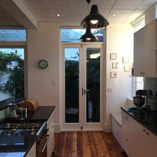 他の地域のヴィクトリアン調のおしゃれなキッチン (アンダーカウンターシンク、フラットパネル扉のキャビネット、白いキャビネット、御影石カウンター、緑のキッチンパネル、ガラスタイルのキッチンパネル、シルバーの調理設備の、無垢フローリング) の写真