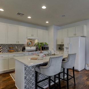 Bild på ett mellanstort funkis linjärt kök och matrum, med en dubbel diskho, släta luckor, vita skåp, bänkskiva i kvartsit, grått stänkskydd, stänkskydd i terrakottakakel, vita vitvaror, laminatgolv, en köksö och brunt golv
