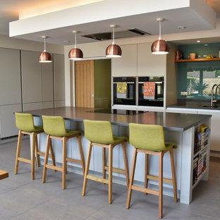 ケンブリッジシャーの中サイズのコンテンポラリースタイルのおしゃれなキッチン (アンダーカウンターシンク、フラットパネル扉のキャビネット、グレーのキャビネット、珪岩カウンター、黒い調理設備、セラミックタイルの床、グレーの床、グレーのキッチンカウンター、緑のキッチンパネル、ガラス板のキッチンパネル) の写真