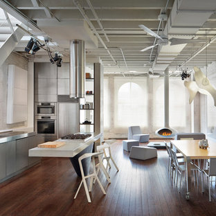Design ideas for an urban galley open plan kitchen in New York with flat-panel cabinets, grey cabinets, stainless steel worktops, an integrated sink, white splashback, brick splashback, stainless steel appliances, dark hardwood flooring, brown floors and multicoloured worktops.