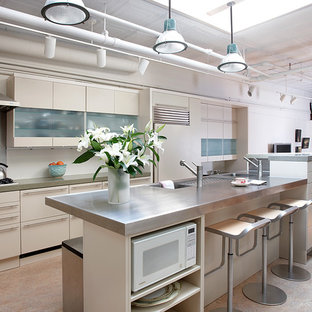 Photo of an industrial open plan kitchen in New York with with island, flat-panel cabinets, beige cabinets, stainless steel benchtops, metallic splashback and panelled appliances.
