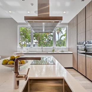 マイアミのモダンスタイルのおしゃれなキッチン (シングルシンク、フラットパネル扉のキャビネット、中間色木目調キャビネット、白いキッチンパネル、シルバーの調理設備、淡色無垢フローリング、ベージュの床、白いキッチンカウンター) の写真