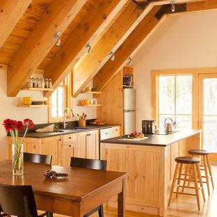 Offene, Einzeilige Landhaus Küche mit Unterbauwaschbecken, beigen Schränken, Küchenrückwand in Schwarz, Küchengeräten aus Edelstahl, braunem Holzboden, Kücheninsel, beigem Boden und schwarzer Arbeitsplatte in Portland Maine