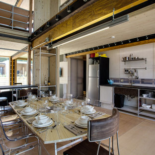 Idée de décoration pour une grande cuisine ouverte linéaire urbaine avec un évier encastré, un placard sans porte, une façade en inox, un électroménager en acier inoxydable, un sol en bois clair et aucun îlot.