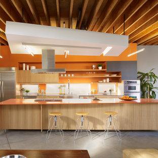 Foto på ett funkis orange parallellkök, med släta luckor, skåp i ljust trä, orange stänkskydd, rostfria vitvaror, betonggolv, en köksö och grått golv