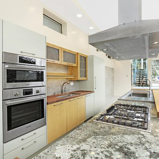 Inspiration for a mid-sized modern galley open plan kitchen in Los Angeles with an integrated sink, flat-panel cabinets, light wood cabinets, granite benchtops, beige splashback, porcelain splashback, stainless steel appliances and with island.