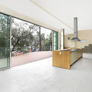 Inspiration för ett mellanstort funkis kök, med en integrerad diskho, släta luckor, skåp i ljust trä, granitbänkskiva, beige stänkskydd, stänkskydd i porslinskakel, rostfria vitvaror, klinkergolv i porslin, en köksö och grått golv