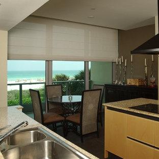 Zweizeilige, Mittelgroße Moderne Wohnküche ohne Insel mit Einbauwaschbecken, flächenbündigen Schrankfronten, hellen Holzschränken, Granit-Arbeitsplatte, Küchengeräten aus Edelstahl, dunklem Holzboden und blauem Boden in Miami