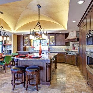 Immagine di una cucina mediterranea di medie dimensioni con isola, ante con riquadro incassato, ante marroni, top in granito, paraspruzzi verde, paraspruzzi con piastrelle in ceramica, elettrodomestici in acciaio inossidabile, pavimento in travertino e pavimento beige