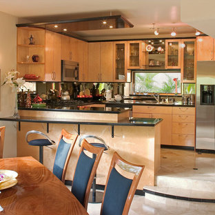 Photo of a small modern u-shaped kitchen/diner in San Diego with a double-bowl sink, glass-front cabinets, light wood cabinets, granite worktops, multi-coloured splashback, mirror splashback, stainless steel appliances, travertine flooring and an island.