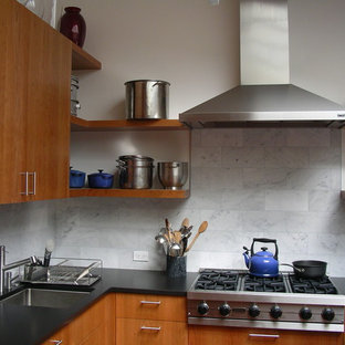 Example of a trendy kitchen design in San Francisco with stainless steel appliances, an undermount sink, flat-panel cabinets, medium tone wood cabinets, white backsplash and marble backsplash