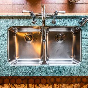 他の地域の中サイズのトラディショナルスタイルのおしゃれなキッチン (ダブルシンク、シェーカースタイル扉のキャビネット、中間色木目調キャビネット、ガラスカウンター、マルチカラーのキッチンパネル、ガラスタイルのキッチンパネル、白い調理設備、テラコッタタイルの床、アイランドなし、オレンジの床、緑のキッチンカウンター) の写真