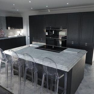 エセックスの大きいヴィクトリアン調のおしゃれなキッチン (アンダーカウンターシンク、シェーカースタイル扉のキャビネット、グレーのキャビネット、大理石カウンター、白いキッチンパネル、大理石のキッチンパネル、黒い調理設備、大理石の床、白い床) の写真