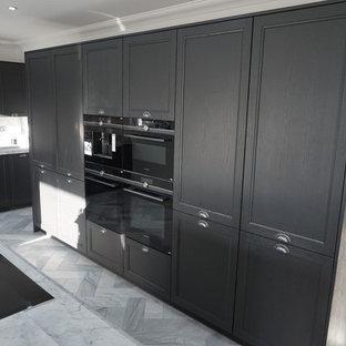 エセックスの広いヴィクトリアン調のおしゃれなキッチン (アンダーカウンターシンク、シェーカースタイル扉のキャビネット、グレーのキャビネット、大理石カウンター、白いキッチンパネル、大理石のキッチンパネル、黒い調理設備、大理石の床、白い床) の写真