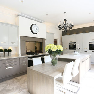 Photo of a large traditional l-shaped kitchen/diner in London with flat-panel cabinets, mirror splashback, stainless steel appliances, an island, beige floors and white worktops.