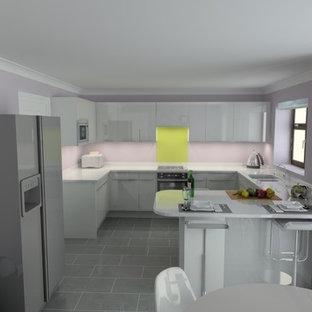 他の地域の中くらいのモダンスタイルのおしゃれなキッチン (一体型シンク、フラットパネル扉のキャビネット、白いキャビネット、人工大理石カウンター、黄色いキッチンパネル、ガラス板のキッチンパネル、シルバーの調理設備、セラミックタイルの床、グレーの床) の写真