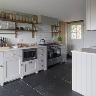 Small rural kitchen in Cornwall with shaker cabinets, grey cabinets, no island, marble worktops, white splashback, metro tiled splashback, stainless steel appliances and black floors.