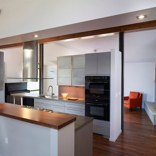 Example of a mid-sized minimalist galley dark wood floor and brown floor open concept kitchen design in DC Metro with black appliances, an undermount sink, flat-panel cabinets, gray cabinets, solid surface countertops and an island