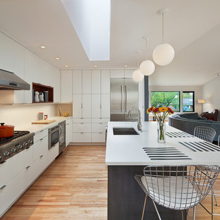 This is an example of a large midcentury u-shaped open plan kitchen in DC Metro with a single-bowl sink, flat-panel cabinets, white cabinets, quartz benchtops, white splashback, ceramic splashback, stainless steel appliances, light hardwood floors, with island and beige floor.
