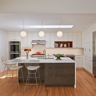 Photo of a mid-sized midcentury l-shaped open plan kitchen in DC Metro with flat-panel cabinets, white cabinets, with island, quartz benchtops, white splashback, ceramic splashback, stainless steel appliances, light hardwood floors, an undermount sink and beige floor.