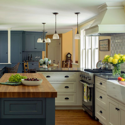 Eat-in kitchen - large country u-shaped medium tone wood floor eat-in kitchen idea in Boston with a farmhouse sink, white backsplash, stainless steel appliances, an island, shaker cabinets, blue cabinets, wood countertops and ceramic backsplash