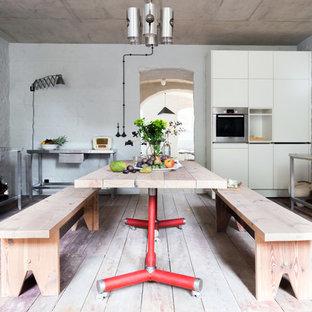 Große Industrial Wohnküche in U-Form mit Edelstahl-Arbeitsplatte, Küchengeräten aus Edelstahl, gebeiztem Holzboden, braunem Boden, flächenbündigen Schrankfronten, weißen Schränken und integriertem Waschbecken in Berlin