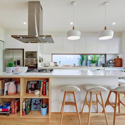 Kitchen - contemporary galley medium tone wood floor and brown floor kitchen idea in Sydney with an undermount sink, flat-panel cabinets, white cabinets, white backsplash, window backsplash, stainless steel appliances, an island and white countertops