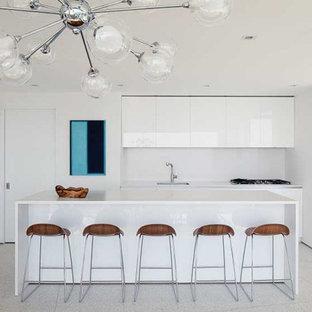 Idéer för att renovera ett stort funkis vit vitt kök, med en enkel diskho, släta luckor, vita skåp, bänkskiva i kvarts, vitt stänkskydd, stänkskydd i porslinskakel, integrerade vitvaror, terrazzogolv, en köksö och grått golv