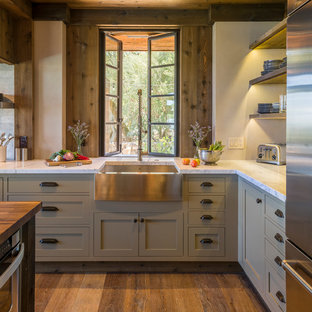 This is an example of a mid-sized country l-shaped kitchen in San Francisco with a farmhouse sink, grey cabinets, marble benchtops, stainless steel appliances and medium hardwood floors.
