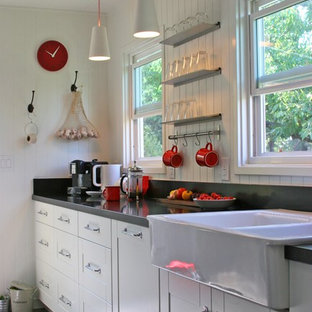 Small transitional galley separate kitchen in San Francisco with a farmhouse sink, shaker cabinets, white cabinets, quartz benchtops, white splashback, timber splashback, stainless steel appliances, porcelain floors, no island and brown floor.