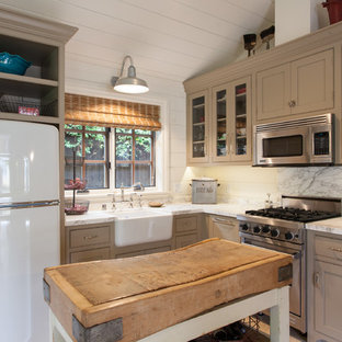 Small farmhouse kitchen appliance - Inspiration for a small country l-shaped kitchen remodel in San Francisco with a farmhouse sink, beaded inset cabinets, stainless steel appliances, an island and beige cabinets