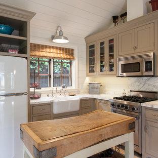 Ejemplo de cocina en L, de estilo de casa de campo, pequeña, con fregadero sobremueble, armarios con rebordes decorativos, electrodomésticos de acero inoxidable, una isla y puertas de armario beige