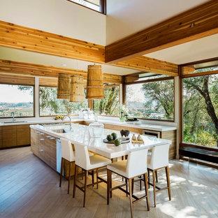 Cette photo montre une cuisine ouverte tendance avec un évier encastré, un placard à porte plane, des portes de placard en bois brun, un sol en bois clair et un îlot central.